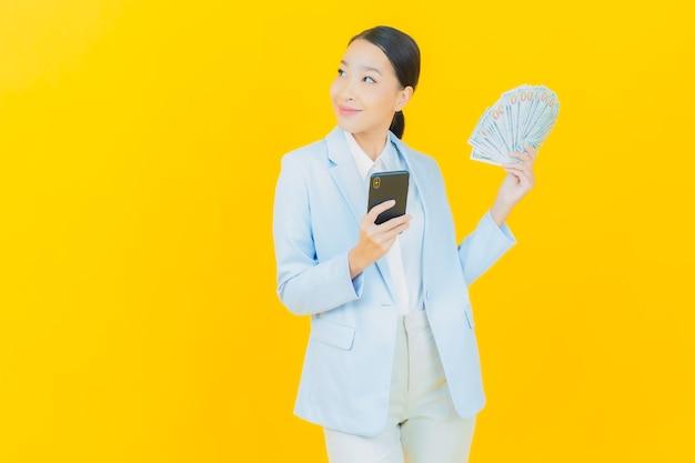 Portret mooie jonge aziatische vrouw glimlach met veel contant geld en geld op geel