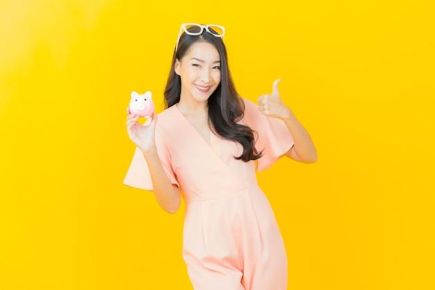 Portret mooie jonge aziatische vrouw glimlach met veel contant geld en geld op kleurenmuur