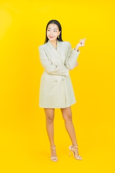 Portret mooie jonge aziatische vrouw glimlacht en poseert op kleurenmuur