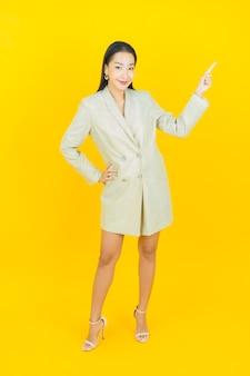 Portret mooie jonge aziatische vrouw glimlacht en wijst omhoog op de kleurenmuur