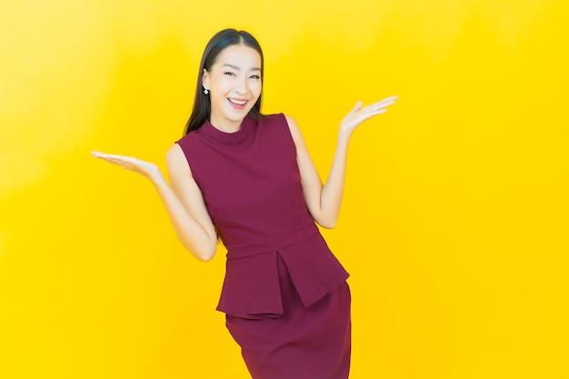 Portret mooie jonge aziatische vrouw glimlacht met actie op gele muur