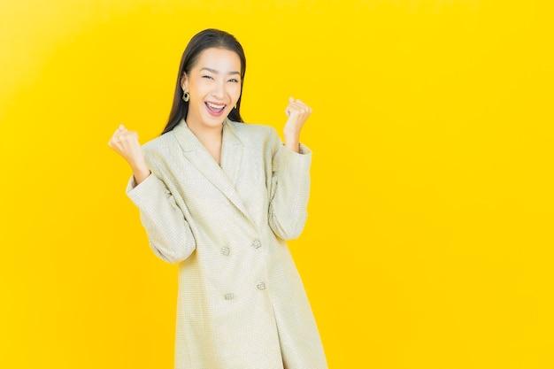 Portret mooie jonge aziatische vrouw glimlacht met actie op kleur muur color
