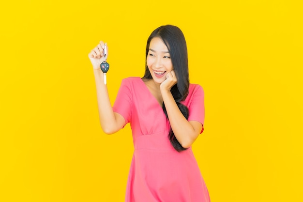 Portret mooie jonge aziatische vrouw glimlacht met autosleutel op gele muur