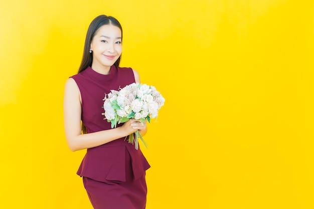 Portret mooie jonge aziatische vrouw glimlacht met bloem op gele muur