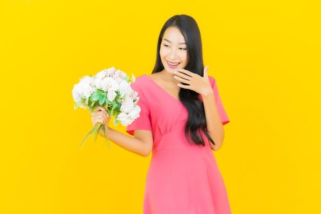 Portret mooie jonge aziatische vrouw glimlacht met boeket bloemen op gele muur