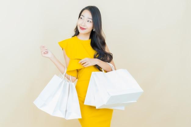 Portret mooie jonge aziatische vrouw glimlacht met boodschappentas op beige muur