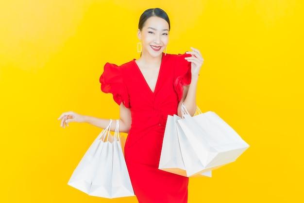 Portret mooie jonge aziatische vrouw glimlacht met boodschappentassen op kleur muur