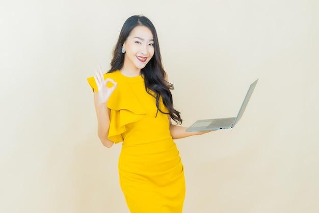 Portret mooie jonge aziatische vrouw glimlacht met computer laptop op geïsoleerde achtergrond
