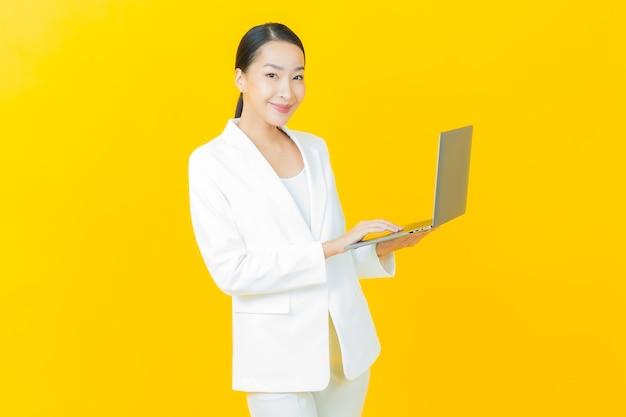 Portret mooie jonge aziatische vrouw glimlacht met computer laptop op geïsoleerde muur