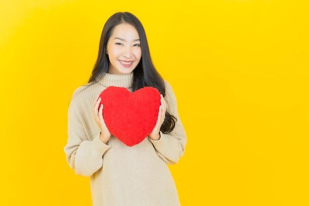 Portret mooie jonge aziatische vrouw glimlacht met hart kussen vorm op gele muur on