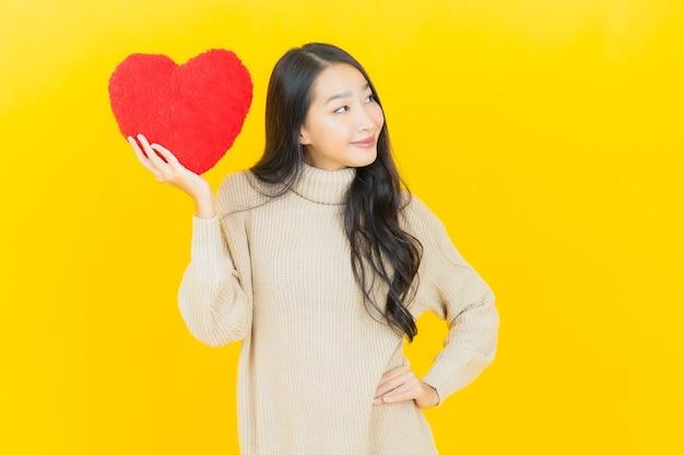 Portret mooie jonge aziatische vrouw glimlacht met hart kussen vorm op gele muur on Premium Foto