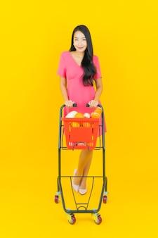 Portret mooie jonge aziatische vrouw glimlacht met kruidenierswinkelmandje van supermarkt op gele muur
