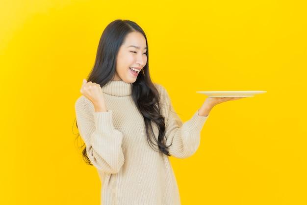 Portret mooie jonge aziatische vrouw glimlacht met lege bordschotel op gele muur