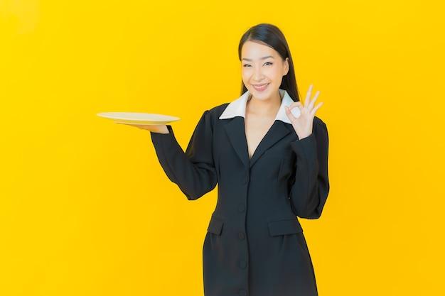 Portret mooie jonge aziatische vrouw glimlacht met lege bordschotel op kleurenmuur