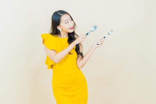 Portret mooie jonge aziatische vrouw glimlacht met lepel en vork op beige muur
