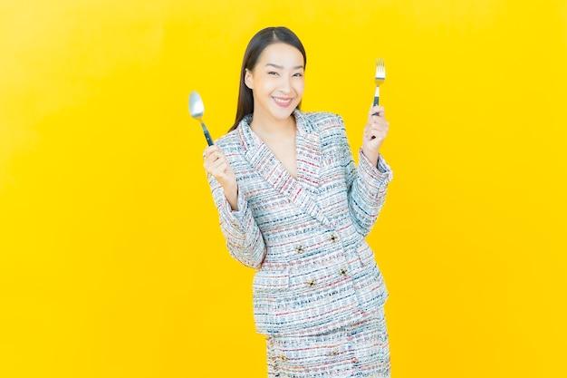 Portret mooie jonge aziatische vrouw glimlacht met lepel en vork op kleurenmuur