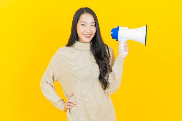 Portret mooie jonge aziatische vrouw glimlacht met megafoon op gele muur yellow
