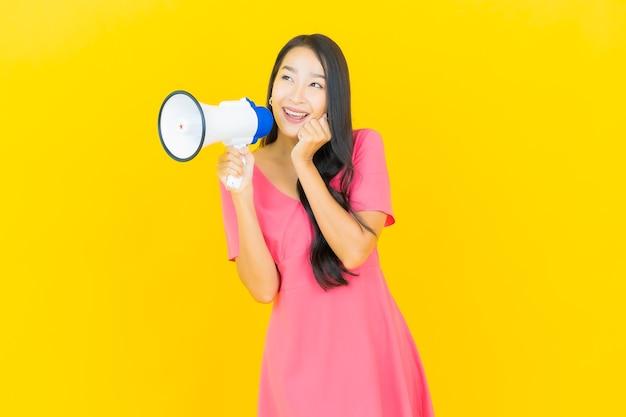 Portret mooie jonge aziatische vrouw glimlacht met megafoon op gele muur