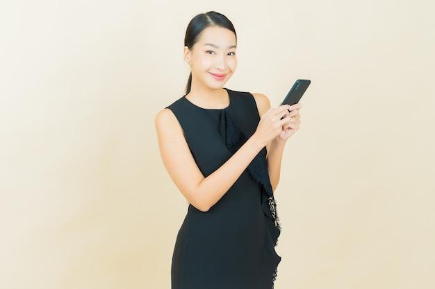 Portret mooie jonge aziatische vrouw glimlacht met slimme mobiele telefoon op kleurenmuur