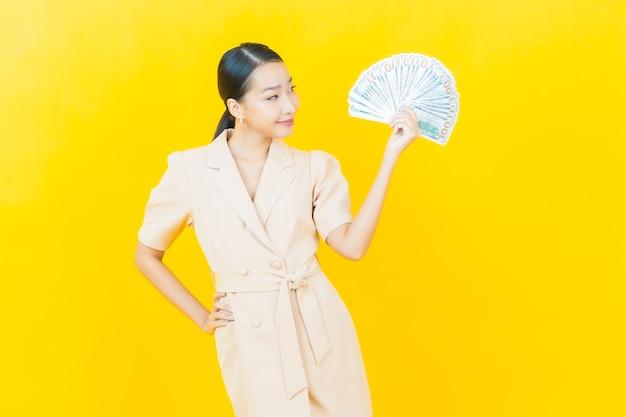 Portret mooie jonge aziatische vrouw glimlacht met veel contant geld en geld op kleurenmuur