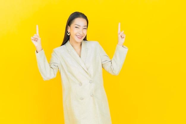 Portret mooie jonge aziatische vrouw glimlacht naar boven op de kleurenmuur