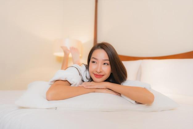 Portret mooie jonge aziatische vrouw glimlacht ontspannen op bed in slaapkamer interieur