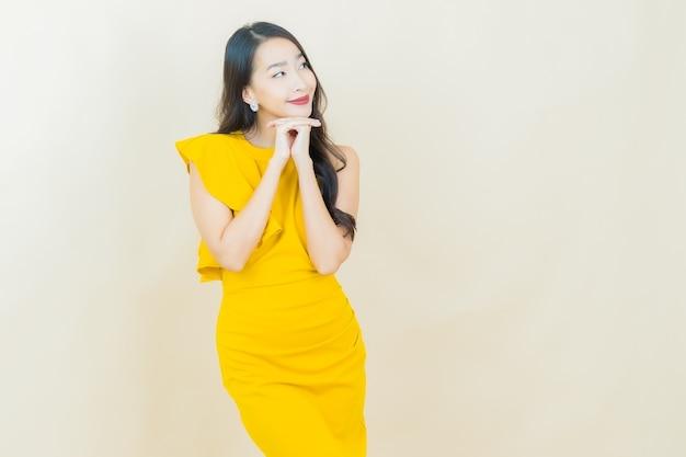 Portret mooie jonge aziatische vrouw glimlacht op beige muur