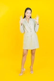 Portret mooie jonge aziatische vrouw glimlacht op gele muur yellow