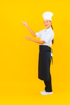 Portret mooie jonge aziatische vrouw in chef-kok of kok uniform met hoed op gele geïsoleerde achtergrond