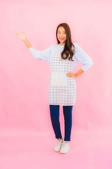 Portret mooie jonge aziatische vrouw in keukenslijtage met schort op roze geïsoleerde muur