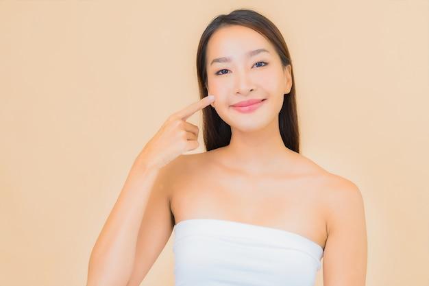 Portret mooie jonge aziatische vrouw in spa met natuurlijke make-up op beige