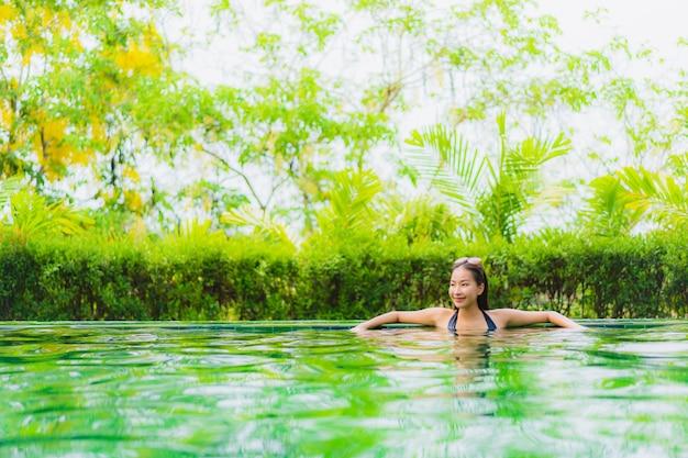Portret mooie jonge aziatische vrouw in zwembad rond hotel en toevlucht