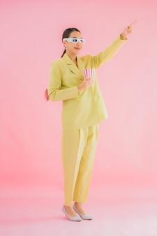 Portret mooie jonge aziatische vrouw met 3d-bril en popcorn klaar voor horloge film op kleur