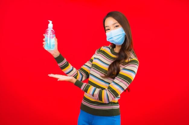 Portret mooie jonge aziatische vrouw met alcoholgel op rode geïsoleerde muur