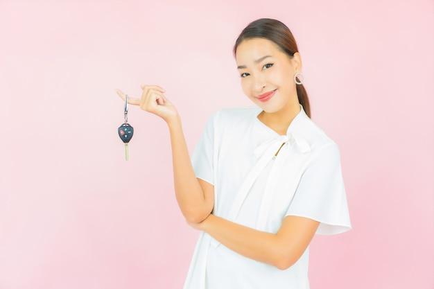 Portret mooie jonge aziatische vrouw met autosleutel op roze kleurenmuur
