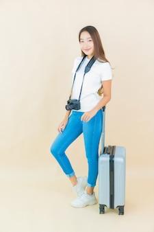 Portret mooie jonge aziatische vrouw met bagage en camera klaar voor reizen op beige