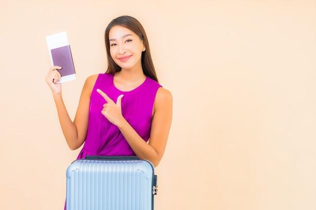 Portret mooie jonge aziatische vrouw met bagage en vliegtuigkaartje op kleurenachtergrond