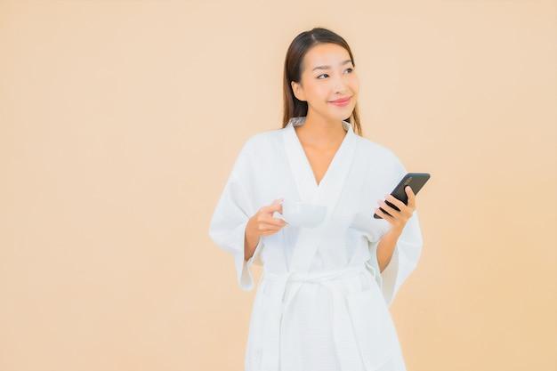 Portret mooie jonge aziatische vrouw met behulp van slimme mobiele telefoon op beige Gratis Foto