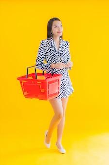 Portret mooie jonge aziatische vrouw met boodschappen mand om te winkelen op geel