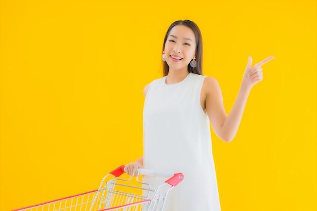 Portret mooie jonge aziatische vrouw met boodschappenmand om te winkelen bij de supermarkt