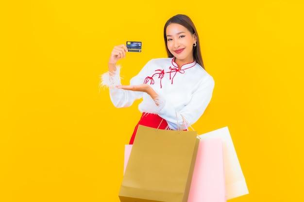Portret mooie jonge aziatische vrouw met boodschappentas en creditcard op geel