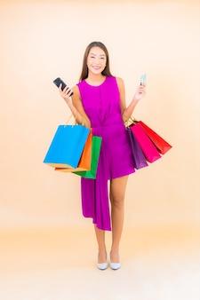 Portret mooie jonge aziatische vrouw met boodschappentas op kleur geïsoleerde achtergrond
