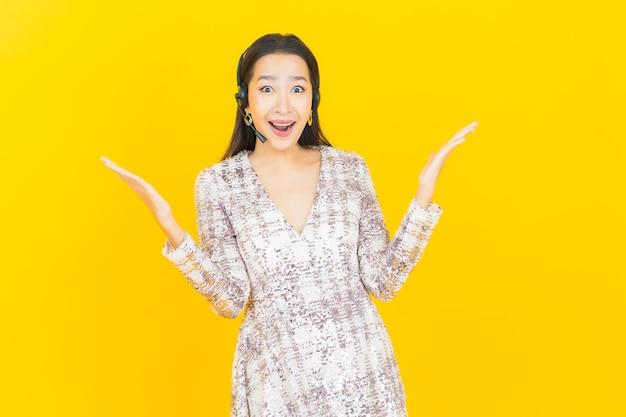 Portret mooie jonge aziatische vrouw met callcenter klantenservice op geel on