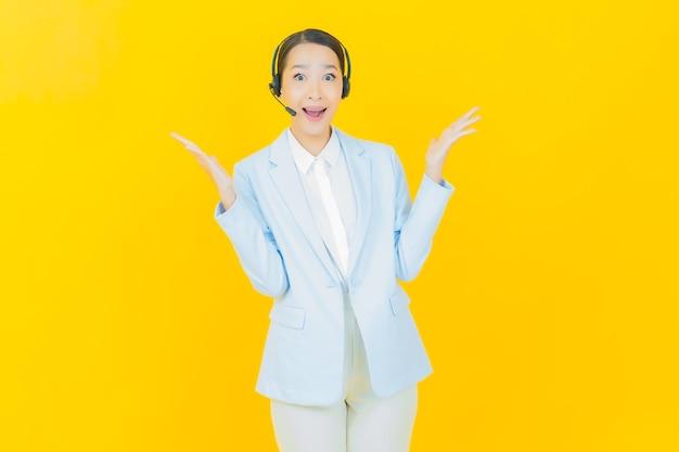 Portret mooie jonge aziatische vrouw met callcenter klantenservice op geel