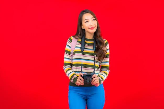 Portret mooie jonge aziatische vrouw met camerarugzak en kaart op rode geïsoleerde muur