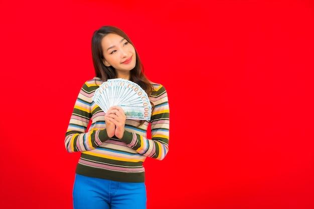 Portret mooie jonge aziatische vrouw met contant geld en mobiele telefoon op rode muur
