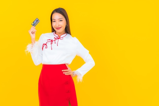 Portret mooie jonge aziatische vrouw met creditcard voor online winkelen op geel
