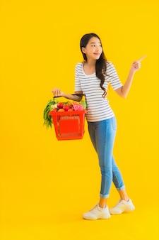 Portret mooie jonge aziatische vrouw met de mand van de kruidenierswinkelmand van supermarkt in winkelcomplex