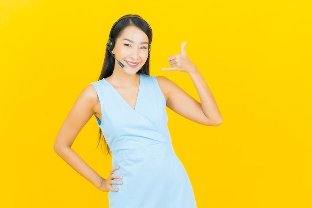 Portret mooie jonge aziatische vrouw met de servicecentrum van de call centre klantenzorg op gele kleurenmuur