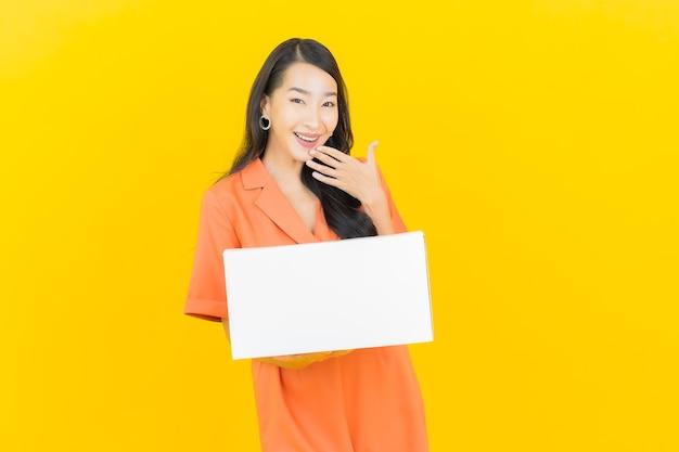 Portret mooie jonge aziatische vrouw met doos klaar voor verzending op geel